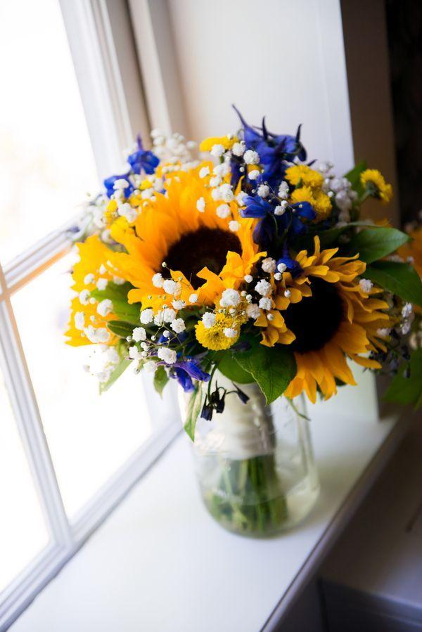 girassol e flores azuis no arranjo perto da janela.