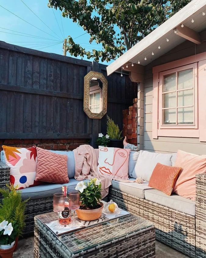 Almofadas e janela rosa na área externa.