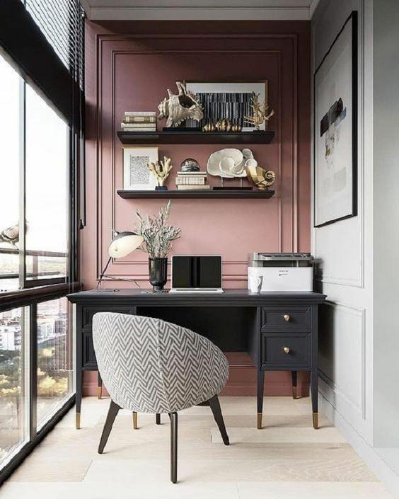 Home office com parede rosa.